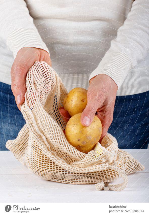 Woman put fresh potatoes in a textile bag Zero waste concept closing woman hands faceless vegetables farmers close up zero food shopping reusable healthy