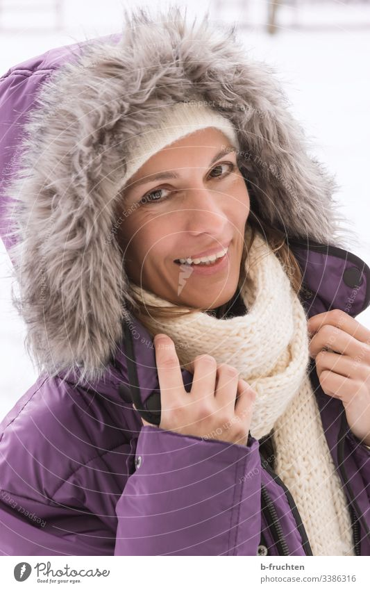 Woman with winter jacket and hood Adults Face portrait Scarf Pelt Coat Jacket Winter Cold hands Laughter Happiness cheerful kind Looking into the camera Comical