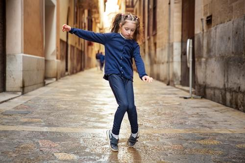 Cute little girl dancing on city street. Narrow streets of Palma de Mallorca old town. active beautiful carefree child childhood children concept cool dance