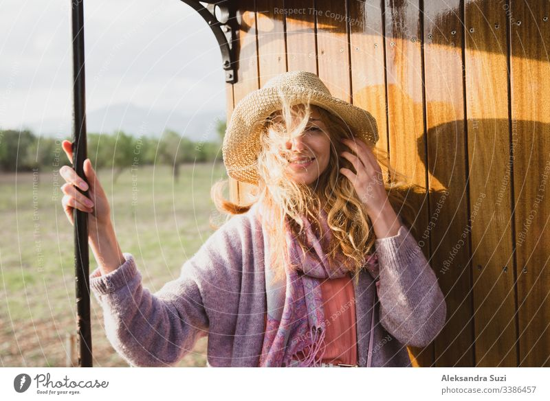 Young woman in straw hat traveling by retro wooden train. Sunset landscape, wind in blond hair. Girl smiling happily. Majorca, Spain. adventure beautiful