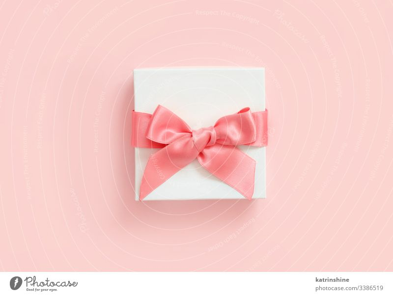 White gift box with a bow on a light pink background white ribbon love romantic top view above present concept creative day decor decoration design floral