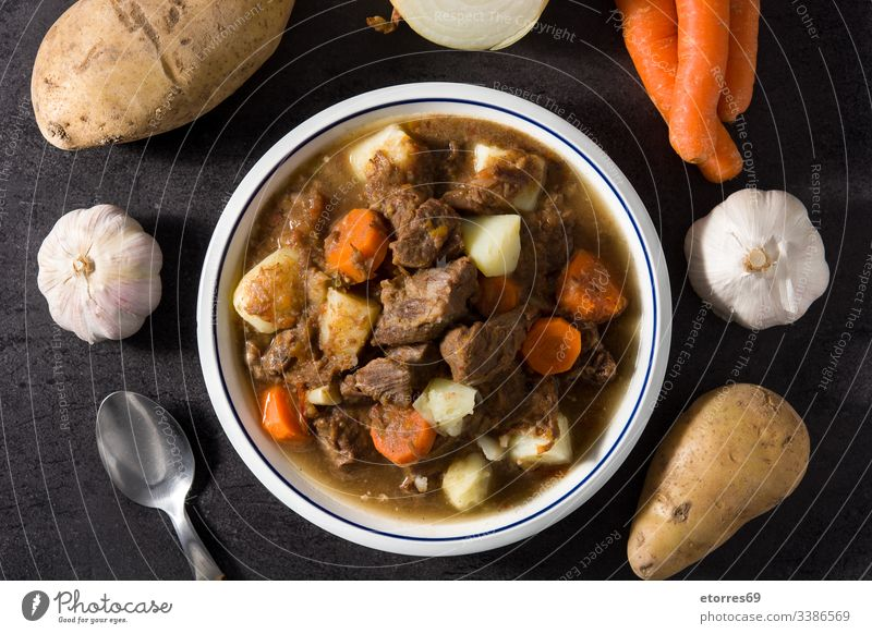 Irish beef stew with carrots and potatoes on black background top view cooked dish food goulash herb homemade irish lamb meat onion plate recipe sauce