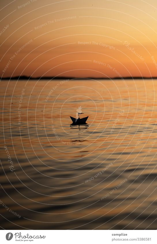 Paper ship at sunset on a lake voyage vacation travel Paper boat Healthy Alternative medicine Wellness Well-being Calm Leisure and hobbies Playing Handicraft