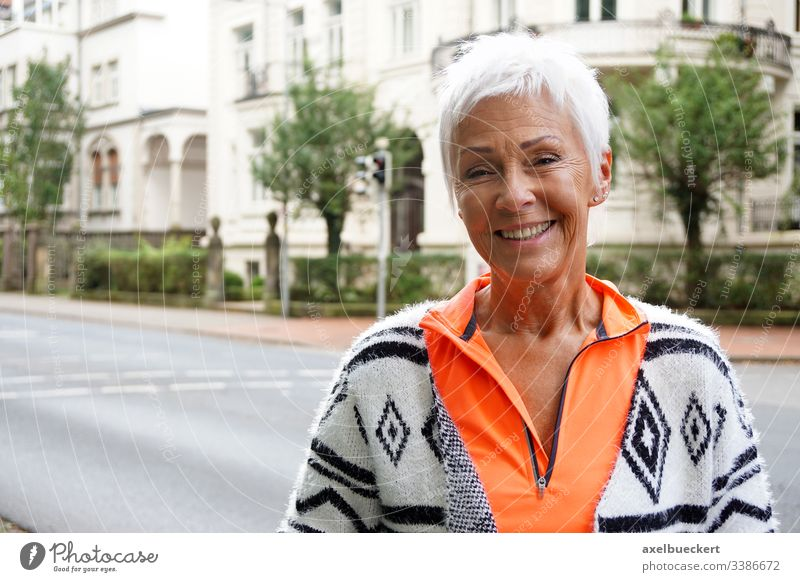 happy mature woman on street senior lady smile outside adult smiling city urban best ager 60 trendy sporty short white hair confident modern sixties cheerful