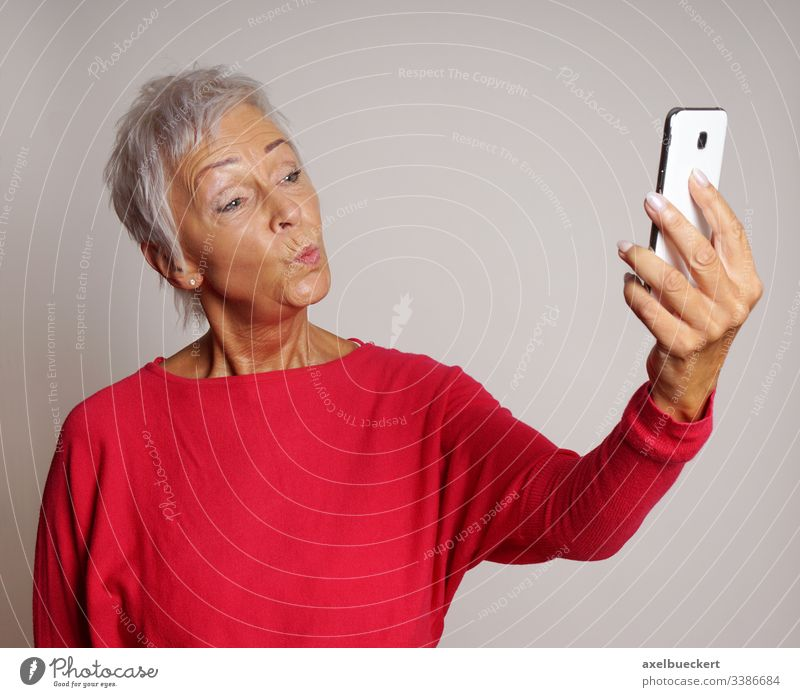 senior woman taking a smartphone selfie with duckface self portrait mature duck face pout mobile cell camera smart phone trend older lady adult photo photograph