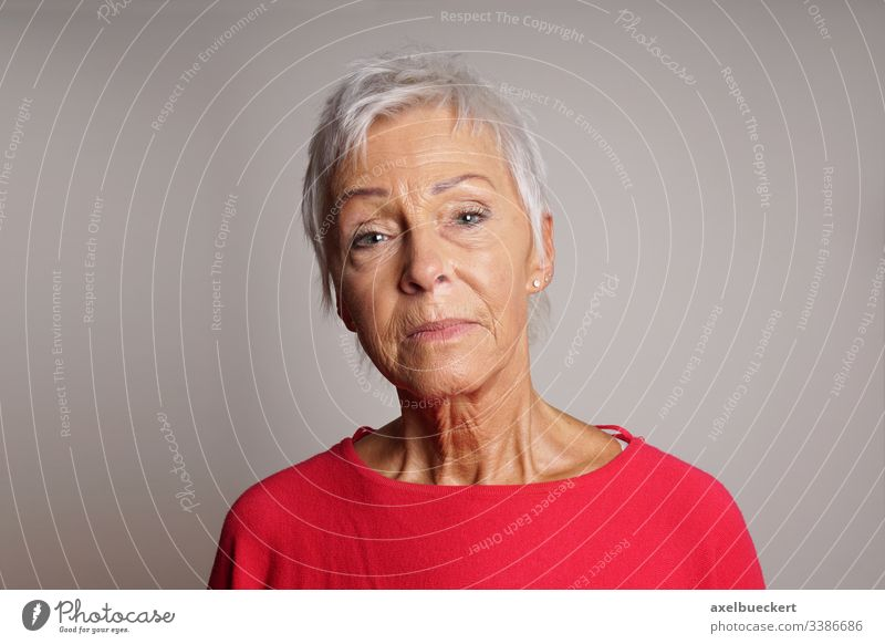 mature woman with her head held high serious senior lady adult 60 sixties older person confident raised unsmiling female people elderly grey gray portrait