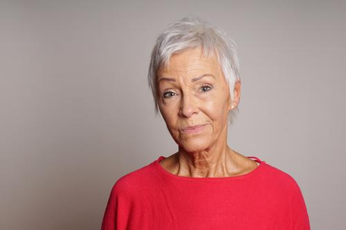 mature woman with skeptical look on her face serious senior lady adult 60 sixties older person sceptic sceptical earnest female people elderly grey gray