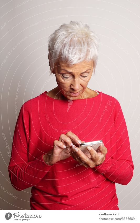 confused senior woman using smartphone mature lady mobile cell smart phone old-timer adult confusion granny grandmother looking at modern technology typing