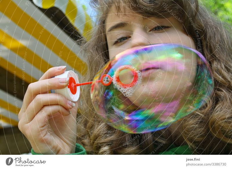 Girl blows big soap bubble Young woman Soap bubble variegated Happiness Ease Free Cheerful Exterior shot Summer Joy Day Dream Playing free time