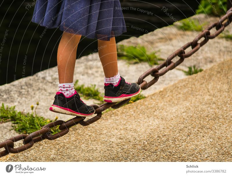 Young girl balancing over a heavy iron chain Girl Legs Skirt young girl Iron chain balance Diagonal Shallow depth of field Copy Space bottom Copy Space right