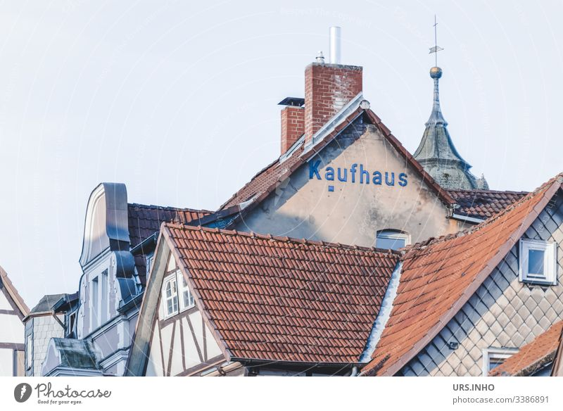 Roofs of old half-timbered houses and gables with the inscription Kaufhaus roofs Brick Half-timbered house Spire chimneys Village Old town Subdued colour