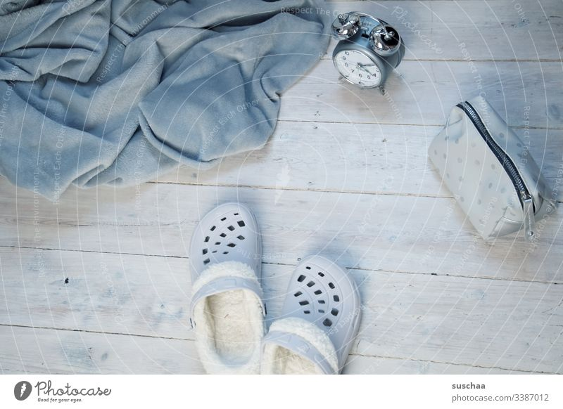grey blanket with slippers, alarm clock and make-up bag on white wooden floor Blanket dwell at home Living or residing Shades of grey House slippers Slippers