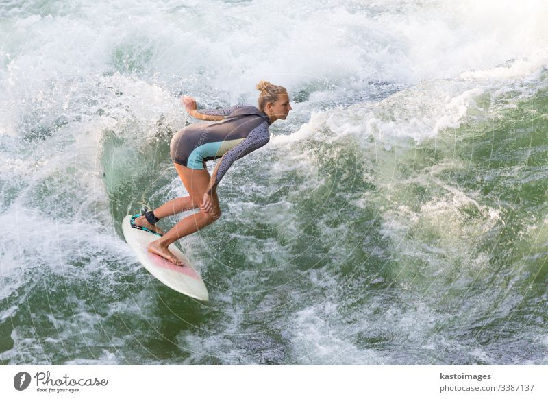 Atractive sporty girl surfing on famous artificial river wave in Englischer garten, Munich, Germany. surfer surfboard woman surfwear summer exercise health