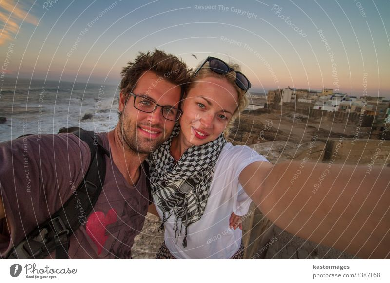 Traveler couple taking selfie on city fortress wall of Essaouira, Morocco. traveler adventure explorer people journey lifestyle freedom outdoor tourism young