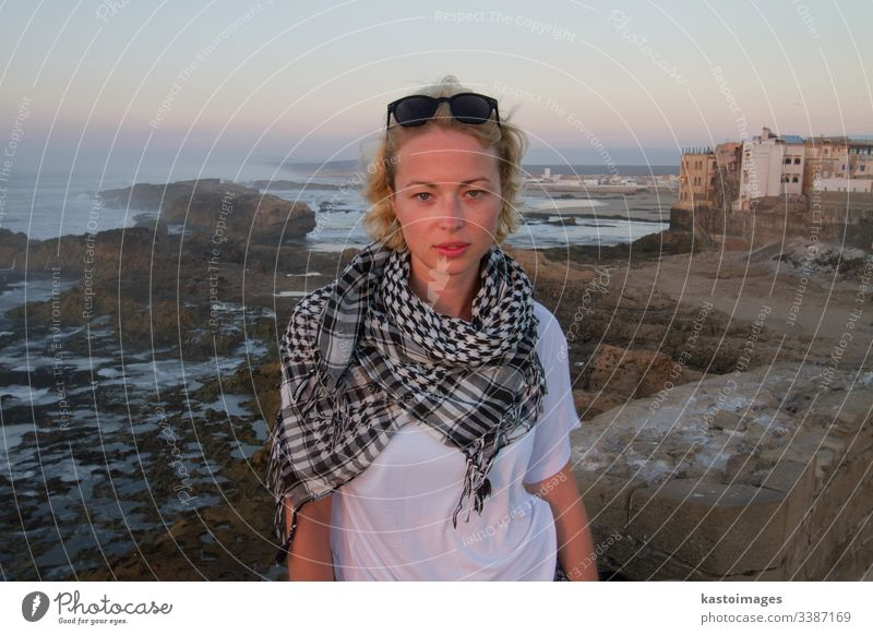 Female traveler standing on city fortress wall of Essaouira, Morocco in sunset. adventure girl explorer journey woman lifestyle freedom outdoor tourism young