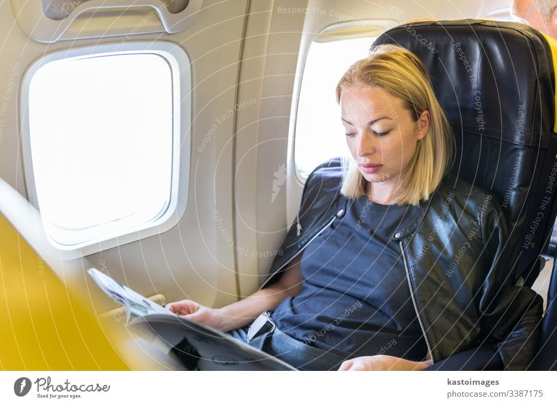 Woman reading magazine on airplane during flight. woman aircraft transport transportation travel trip seat passenger girl interior newspaper window cabin