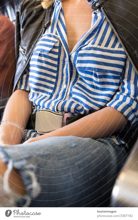 Female passenger with seat belt fastened while sitting on airplane for safe flight. safety travel woman female fly transport girl seatbelt transportation