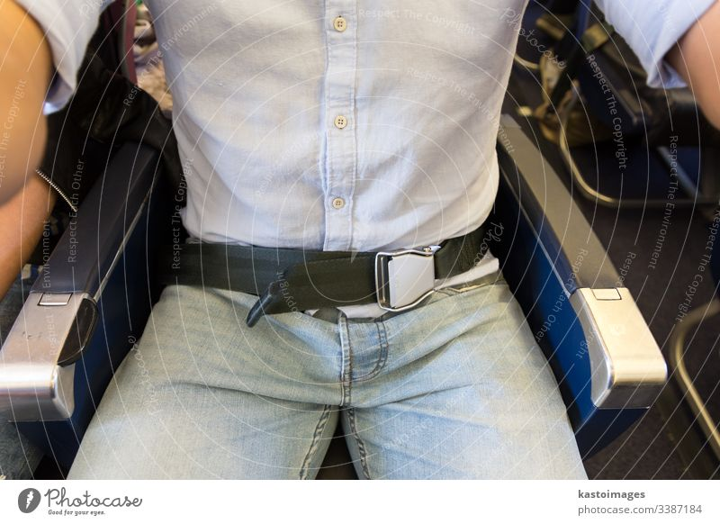 Male passenger with seat belt fastened while sitting on airplane for safe flight. safety protection security seatbelt turbulence airline buckle cabin caution
