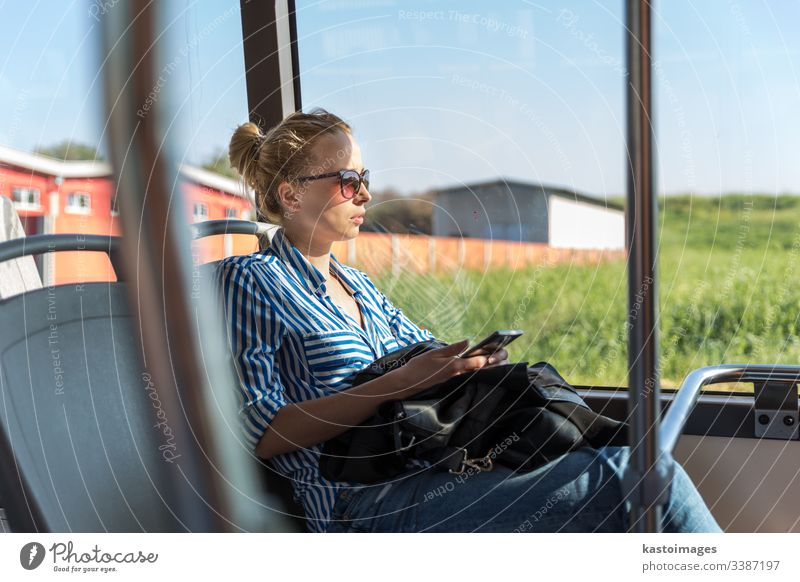 Portrait of woman driving on moving bus sitting by window using mobile phone. passenger female commuter girl transportation inside journey people person tired