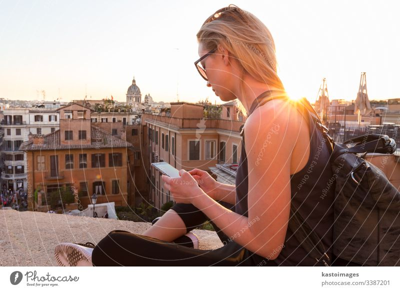Female tourist using mobile phone travel app close to Piazza di Spagna, landmark square with Spanish steps in Rome, Italy at sunset. rome Spanish square woman