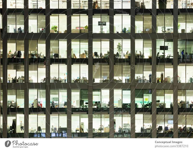 Modern office building at dusk, revealing the daily activity of the workers office block exterior overworked business people ambition architecture