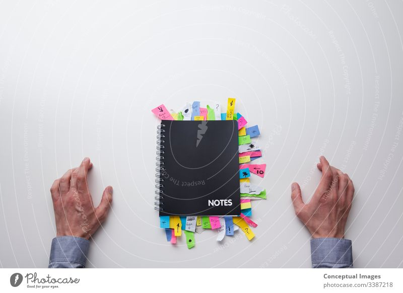 Top view of a man in front of a note pad full of sticky notes adhesive analysis appointment brainstorm brainstorming business busy collaboration color concepts