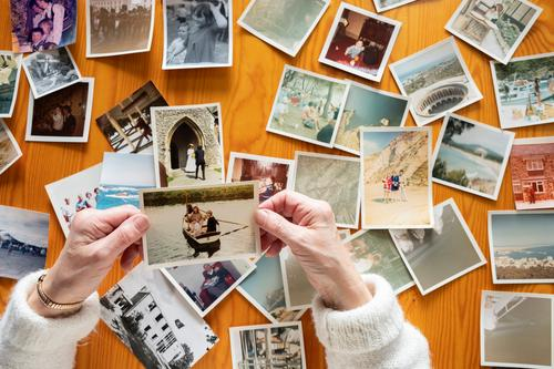 Top view of a senior caucasian woman looking at an old photos themes of memories nostalgia photos retired picture elderly wife together pensioner family