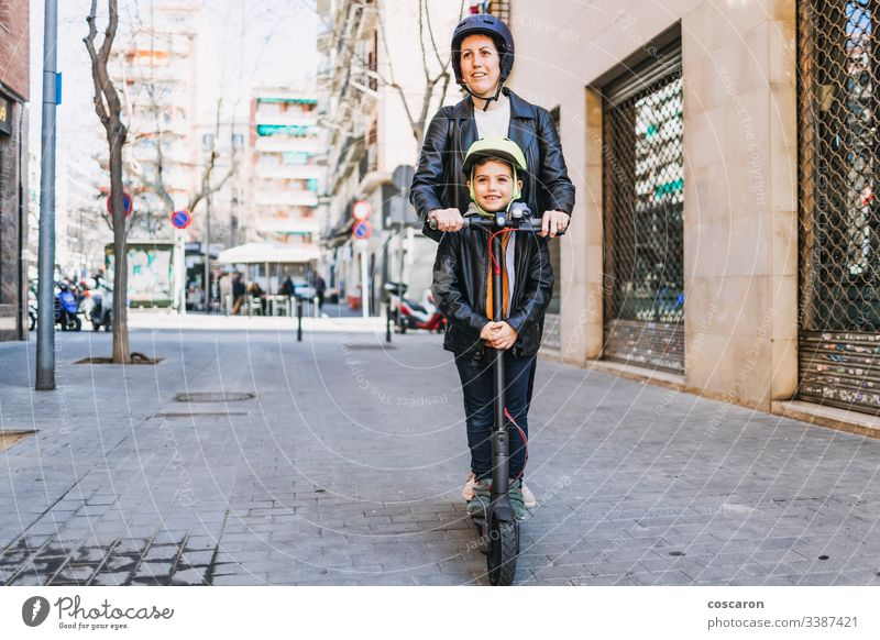 Mother and son riding an electric scooter with helmets active boy casual child city day e-scooter eco europe family female fun generation kick kick scooter