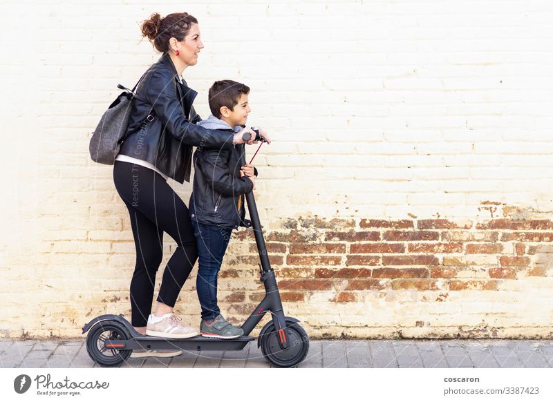 Mother and son riding an electric scooter active boy casual child city day e-scooter eco europe family female fun generation kick kick scooter leisure lifestyle