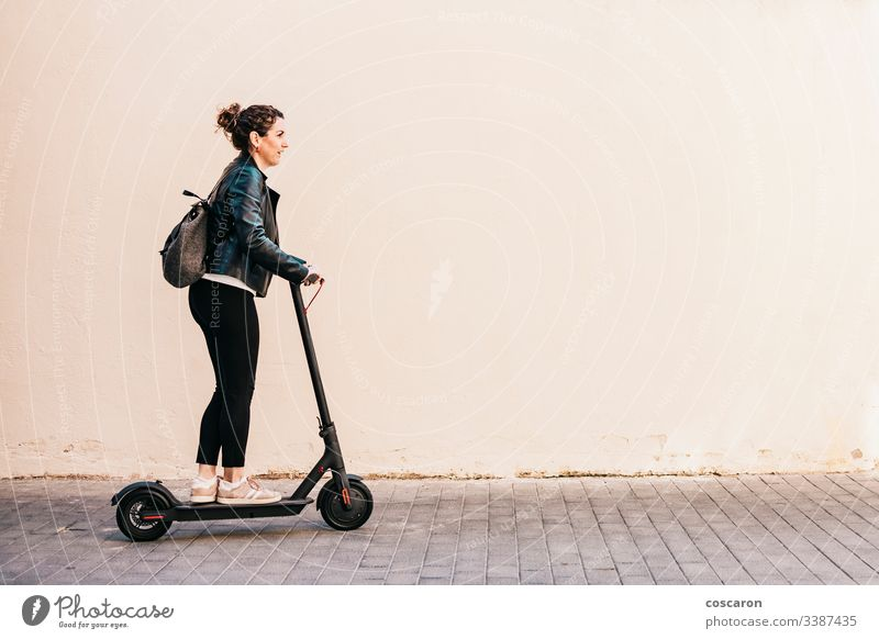 Middle aged woman riding an electric scooter active adult alone attractive background board business cheerful city driving e scooter eco electrical equipment