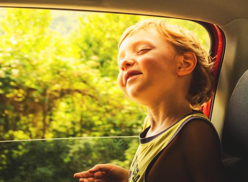 Little caucasian boy enjoying sun and wind travelling in a car with open window. little child happy skin emotion moment hair summer sunny day light t-shirt
