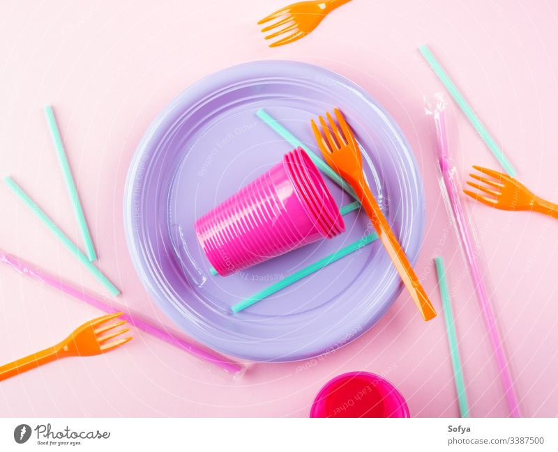Disposable colorful plastic dish, straws and cups, cutlery. Flat lay on pink background. disposable tableware plate ban pollution throw flat lay stop garbage