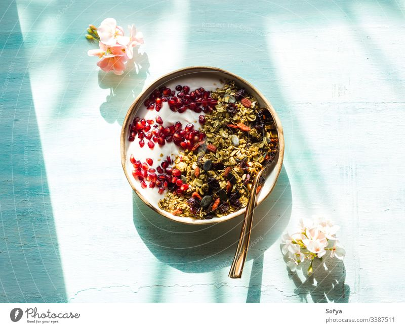 Home made granola bowl with pomegranate seeds, matcha granola with oats and dried fruit, nuts on turquoise background with pink flowers. breakfast delicious