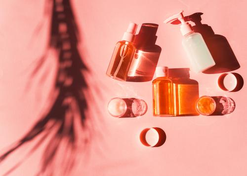 Various cosmetic products in bottles and mini jars on pink coral. Flat lay shot in hard light with plant shadow. skin flat lay orange cream care golden yellow