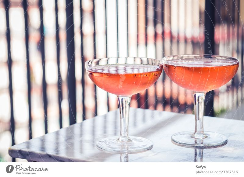 Two crystal stemmed glasses with rose wine on marble table outdoors. Aperitif time white party pink drink dinner luxury light background modern alcohol bar