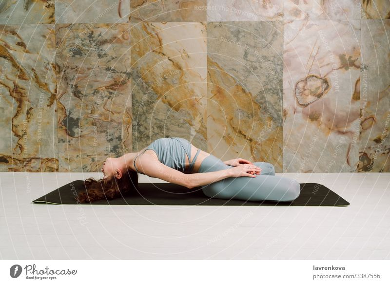 Young yogini practicing Matsyasana pose in pastel blue leggins and top, selective focus active athlete athletic attractive body brunette calm caucasian exercise