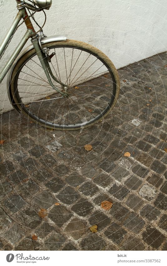 alt l old, nostalgic wheel in retro style, parked in front of a white, bright house wall on cobblestone. front part, lamp, light, tyre of grey wheel parked in the city.danger of theft of old bike, unsecured, not locked in autumn