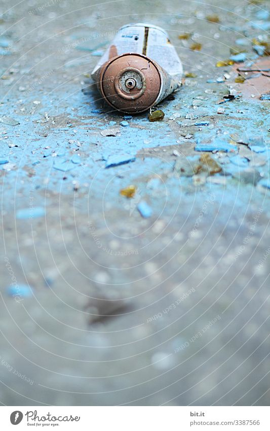 alt l old, blue, cracked, empty spray can, lies on morbid, flaked, broken blue background Environmental sin, pollution, garbage, scrap by carelessly, irresponsibly thrown away paint can in Lost Place. Non-degradable scrap metal.