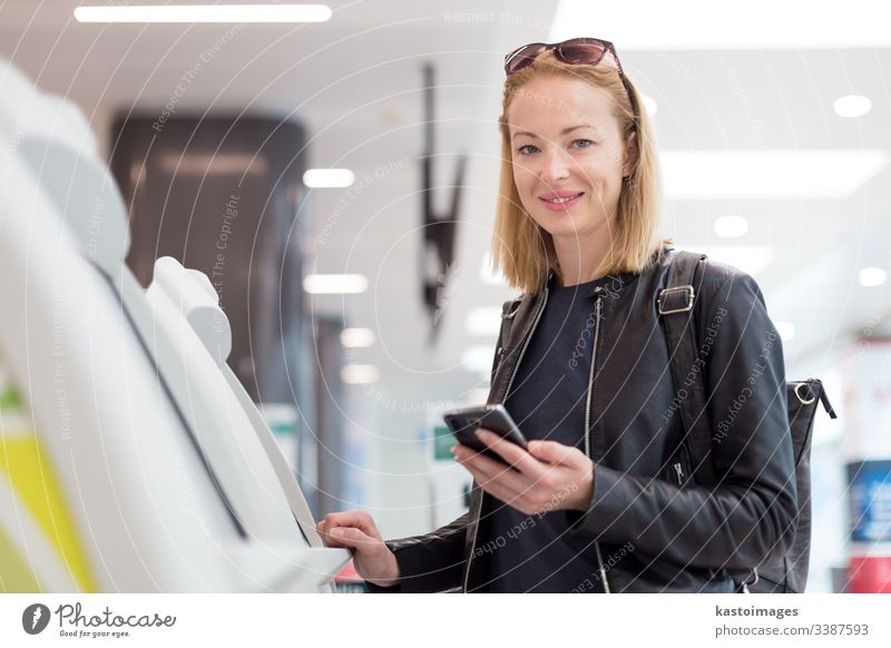 Casual caucasian woman using smart phone application and check-in machine at the airport getting the boarding pass. departure self technology service modern