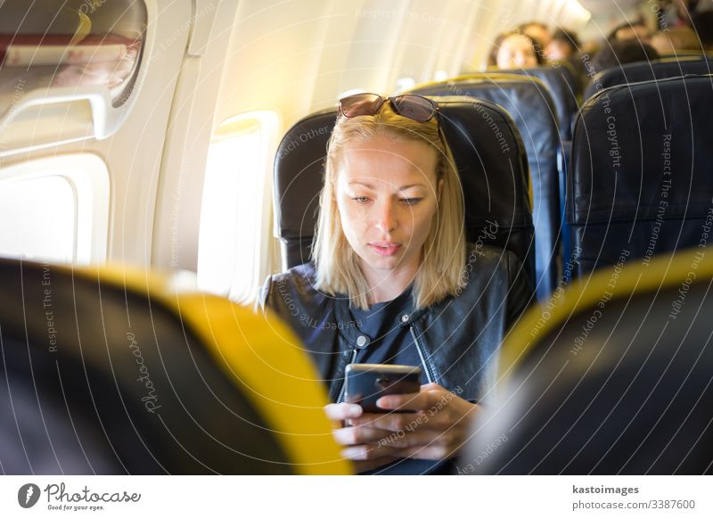 Woman using mobile phone as entertainment on airplane during commercial flight. woman look looking aircraft transport transportation travel trip sunglasses seat