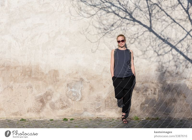 Graphical and textured artisic image of modern trendy fashionable woman wearing sunglasses leaning against old textured retro wall with tree shadow falling on the wall.
