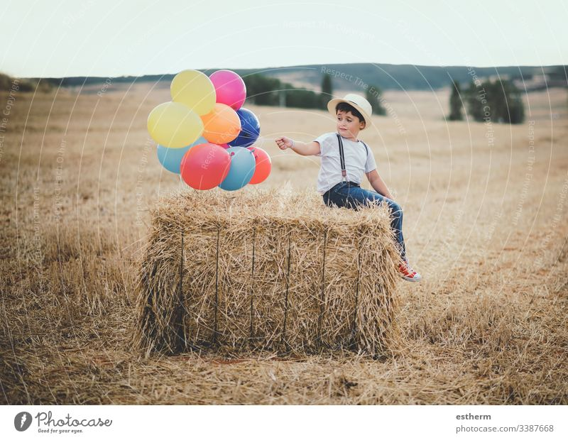 happy child with balloons in the field adventure discover freedom grain grass growth happiness hat independence joy lifestyle multicolored outdoors party play