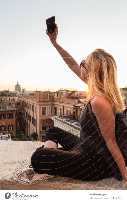 Female tourist taking mobile phone photo of Piazza di Spagna, landmark square with Spanish steps in Rome, Italy at sunset. rome Spanish square self portrait