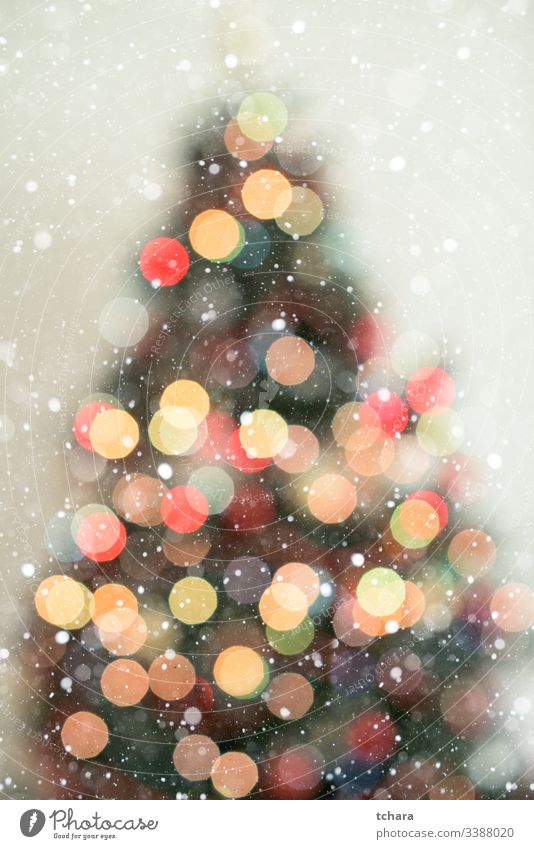 Bokeh christmas tree background with snowfall decorate festive vibrant illumination vivid magic beauty celebrate shapes ornament smooth glittering