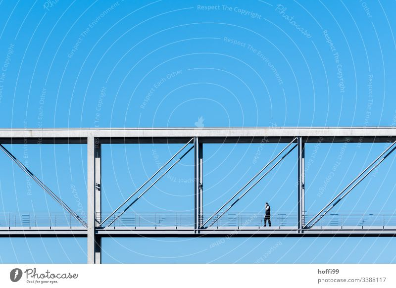 man walk across a minimalistic bridge with deep blue sky Looking away Neutral Background Berlin Esthetic Concrete construction Reichstag Downward Bridge