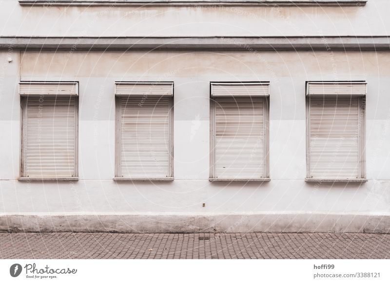 desolate exterior facade with closed blinds Gray Gloomy dreariness bleak jalousin Venetian blinds Roller shutter gray wall Unadorned Lonely depression