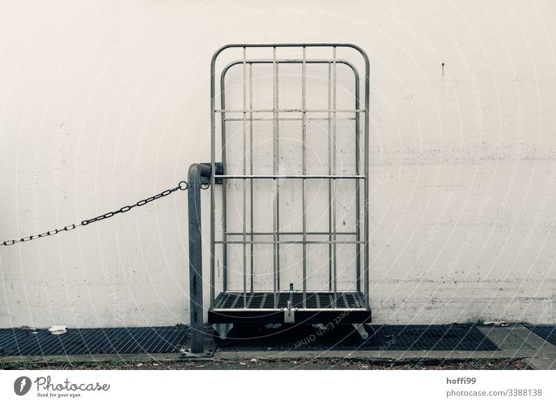 empty trolley with chain and steel tube Delivery truck Chain Gray Gloomy dreariness urban Exterior shot Deserted white wall Wall (building) dirt off-white