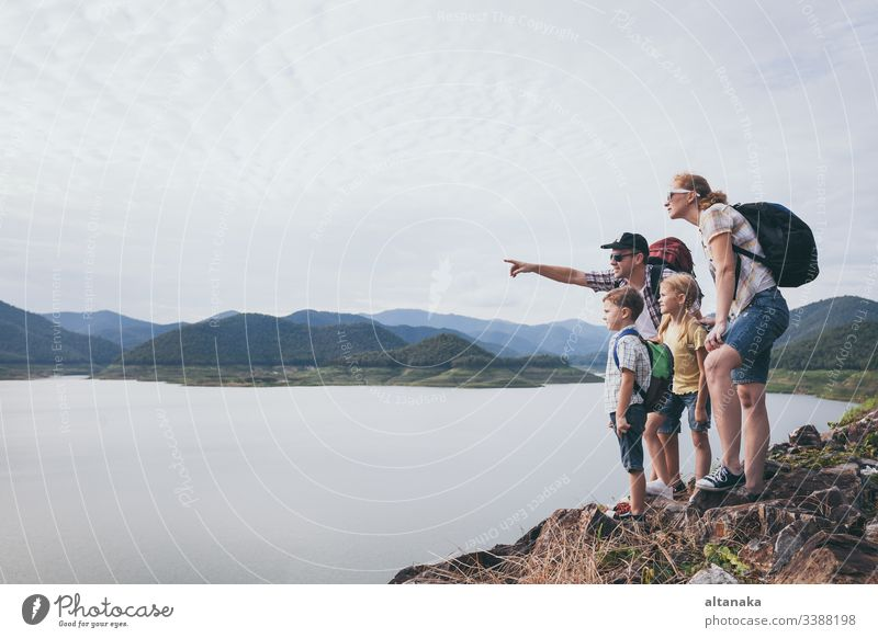 Happy family standing near the lake at the day time. outdoor travel child people son lifestyle vacation boy nature father together active summer dad kid trip