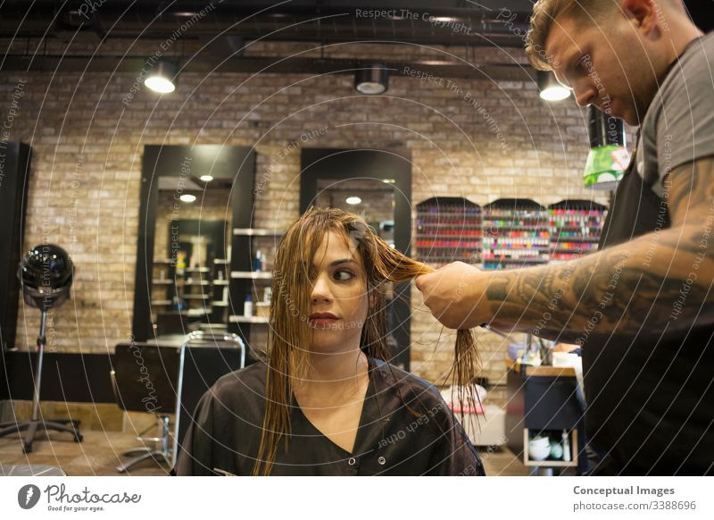 Caucasian woman having her hair styled in a hipster barbershop themes of hairstylist pampering glamour haircare haircut salon hairdressing hairdresser hairstyle