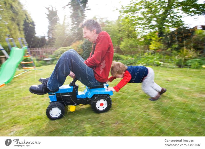 A young boy pushing a man on a toy tractor action adventure blurred motion bonding carefree caucasian cheerful child childhood cooperation determination driving